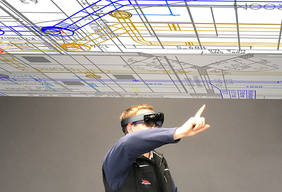 Mithilfe der AR-Datenbrille kann dieser Klimatechniker durch Wände und Decken sehen sowie mit einfachen Fingergesten Baupläne ändern. Foto und Montage: AnyMotion