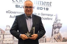 """Staatsrat Henning Lühr freut sich über die Auszeichnung mit dem """"Digital Transformation Award"""" Quelle: Pressereferat, Der Senator für Finanzen"""