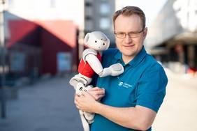 """Thorsten Weber von CONTACT Software mit einem """"Spieler"""" des B-Human-Teams der RoboCup Standard Platform Liga."""