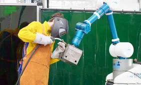 FourByThree-Prototyp in der Anwendungsstudie bei der Firma WOLL: Der Roboterarm unterstützt einen Menschen bei Schweißarbeiten durch Halten und Positionieren des Werkstücks während des Schweißprozesses. Foto: FourByThree