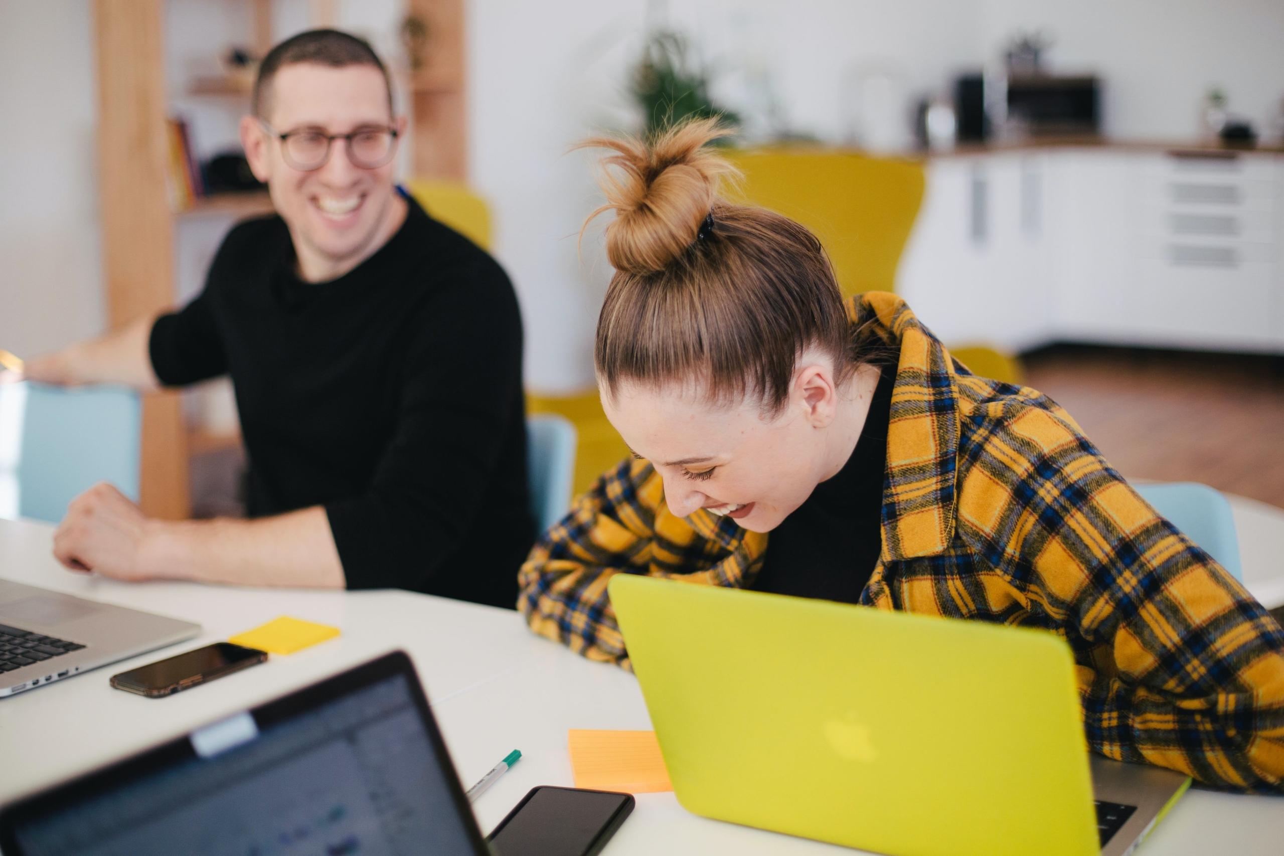 Jungen Menschen sitzen am Schreibtisch vor einem Laptop und lachen.