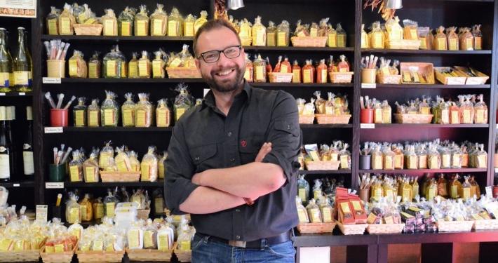 Daniel König, Gründer und Geschäftsführer der Bremer Gewürzhandel GmbH, steht in seinem LAden vor dem Gewürzregal.