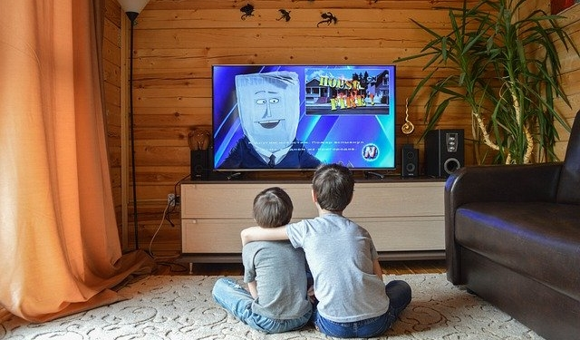 Zwei Kinder sitzen vor einem Fernseher
