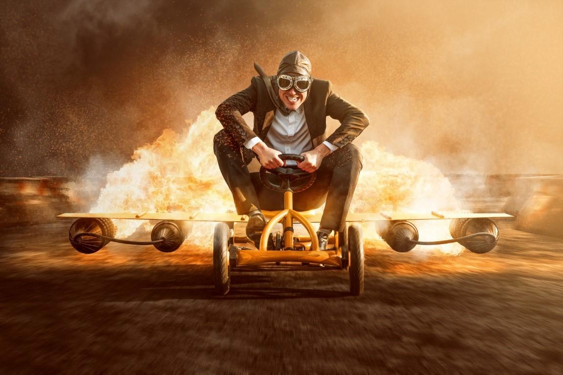 Ein Mann im Anzug auf einem Kinder-Go-Car fährt mit Turboantrieb auf den Betrachter oder die Betrachterin zu.