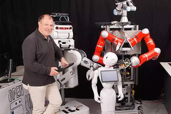 Professor Michael Beetz steht inmitten verschiedener Roboter