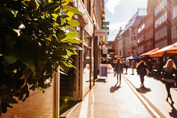 Foto einer Einkaufsstraße mit Menschen, die sie entlanglaufen.