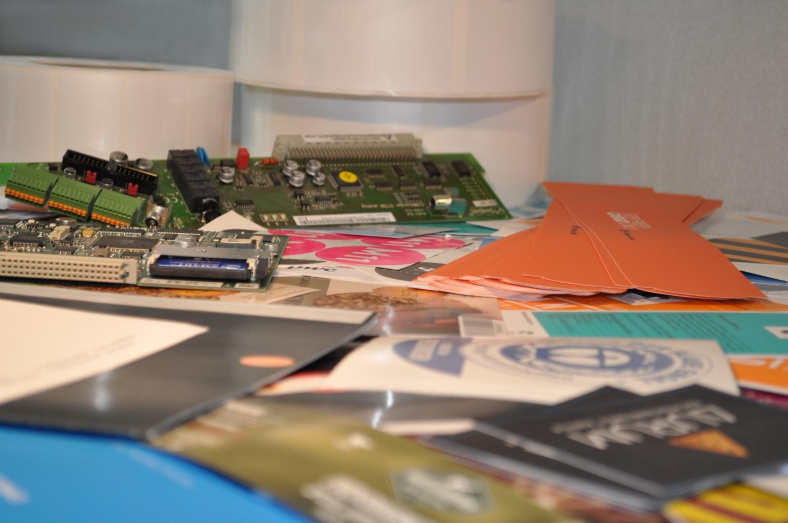 Bild mit verschiedenen Druckmaterialien: Papier, Aufklebern und einiges mehr.