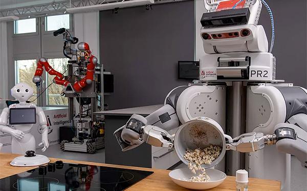 Ein Roboter steht in einer Labor-Küche und schüttet Popcorn in einen Teller.