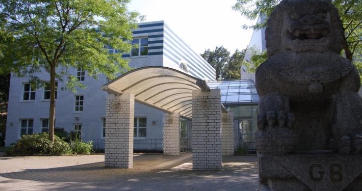 Überdachter Gebäudeeingang mit Bäumen auf der linken und rechten Seite