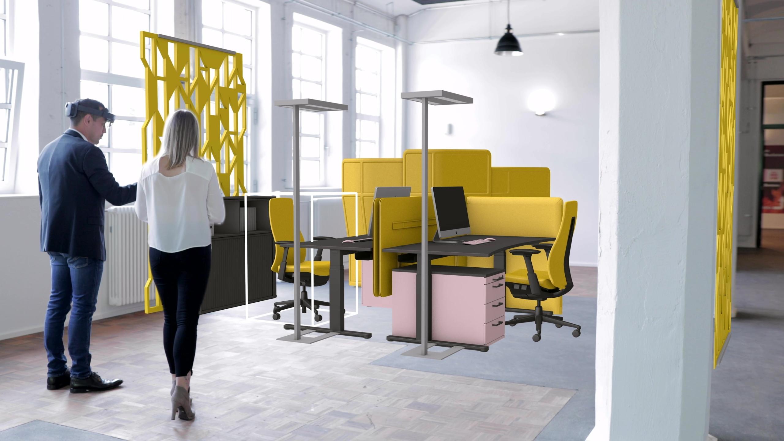 Eine Frau und ein Mann stehen in einem hellen Raum. MIthilfe von Mixed Reality ist eine Büroeinrichtung in den Raum projeziiert.