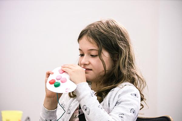Ein in etwa zehnjähriges Mädchen hält prüfend einen selbst gebastelten Controller aus Pappe und Knete in der Hand.