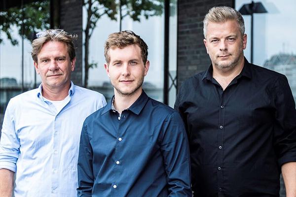 Drei weiße Männer in blauen Hemden stehen nebeneinander.