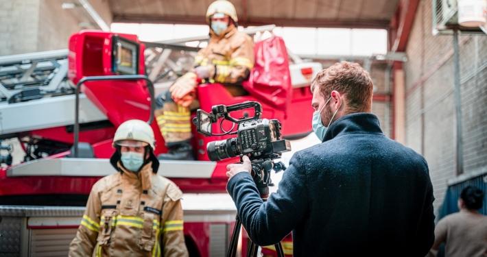 Zwei Feuerwehrleute in Monturwarten auf Anweisungen eines Filmemachers im Vordergrund der hinter seiner Kamera steht.